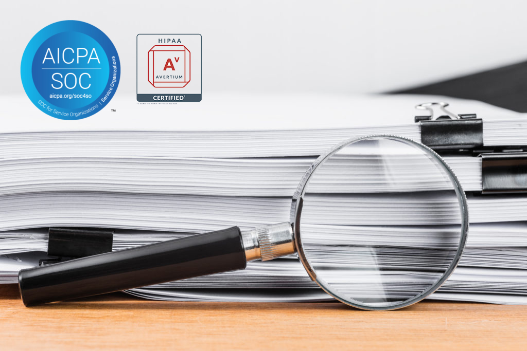 Magnifying glass and clipped documents on a table. AICPA SOC and HIPAA certification badges.
